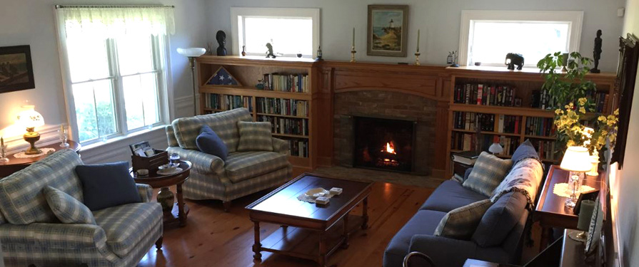 The living room includes spacious seating, fireplace, library, and board games