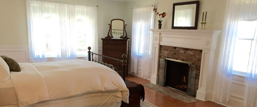 The Coffey House Suite includes a wrought iron bed, fireplace, and sitting area